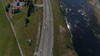 Cars drive down a road that runs alongside a river thumbnail