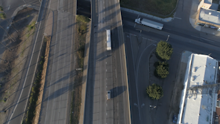 Cars drive down a highway that's running through a city thumbnail