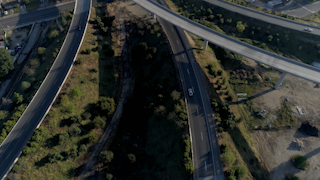 Cars drive over a freeway interchange near a neighborhood thumbnail