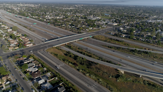 Cars drive down a freeway in a city thumbnail