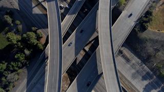 Cars drive through a freeway interchange thumbnail