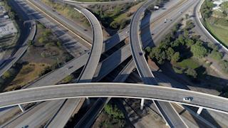 Cars drive through a large freeway interchange in a city thumbnail