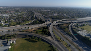 Cars are driving through a large freeway interchange thumbnail