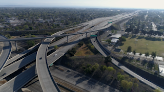 Cars are driving down a freeway in a city thumbnail