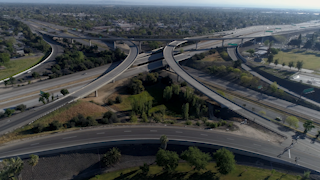 Cars are driving through a highway interchange in a city thumbnail