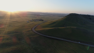 Cars drive down a country road during sunrise thumbnail