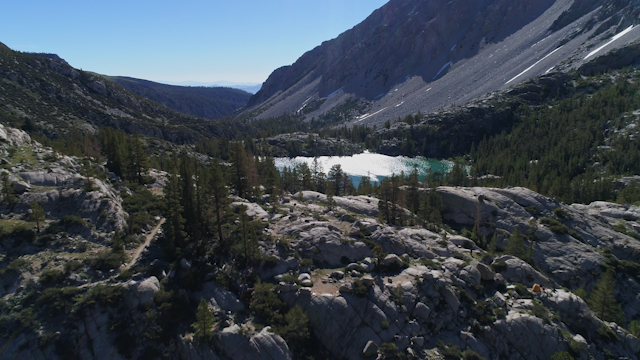 A lake surrounded by trees and mountains thumbnail