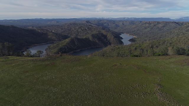 A river flows through a green foothill terrain thumbnail