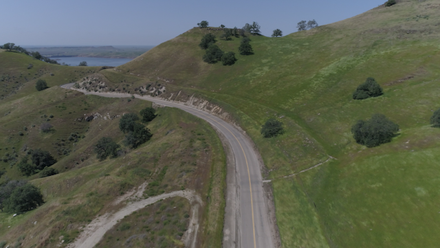A car drives along a curvy road through the foothills thumbnail