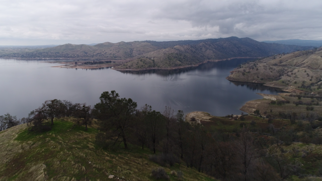 A lake is surrounded by foothills on a cloudy day thumbnail