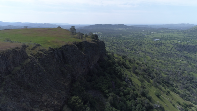 A rocky table top mountain overlooks green foothills and plains thumbnail
