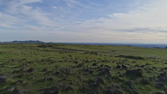 A green rocky field under a partly clouds sky thumbnail