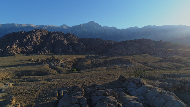 A rocky desert terrain and a mountain range thumbnail