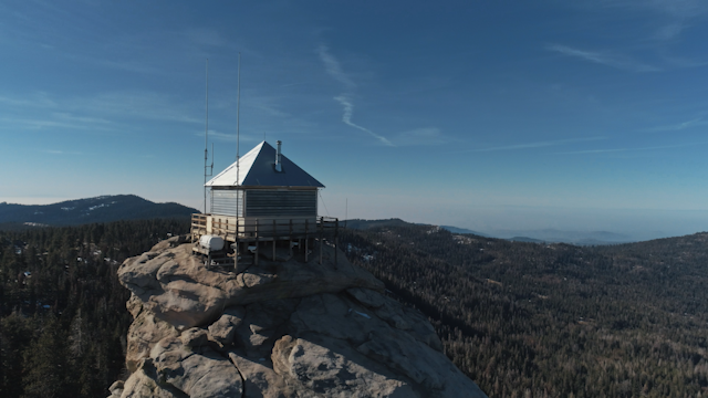A small shack is perched on top of a large rock thumbnail