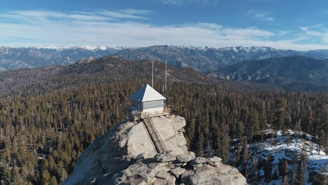 A small shack on a rock overlooks a mountainous horizon thumbnail
