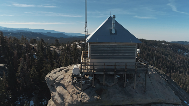 A shack on a rock is surrounded by forest and mountains thumbnail