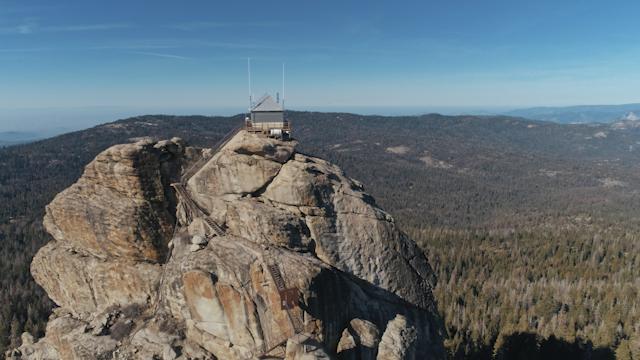 A shack on a rock overlooks a vast wilderness thumbnail