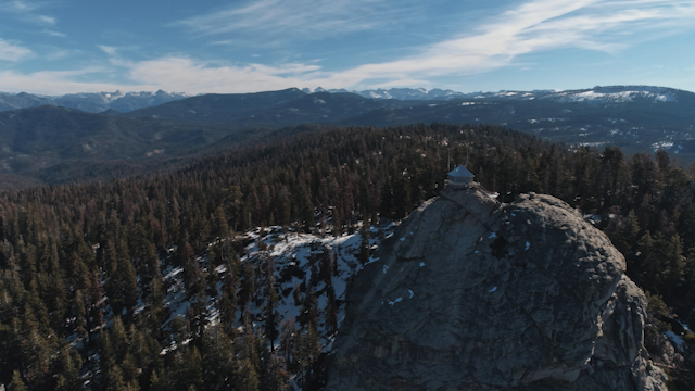 A large rock with a shack on top towers over a forest thumbnail