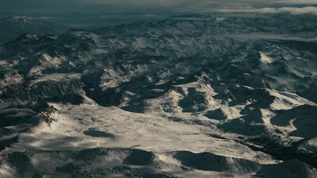A snowy mountain range passes by below thumbnail