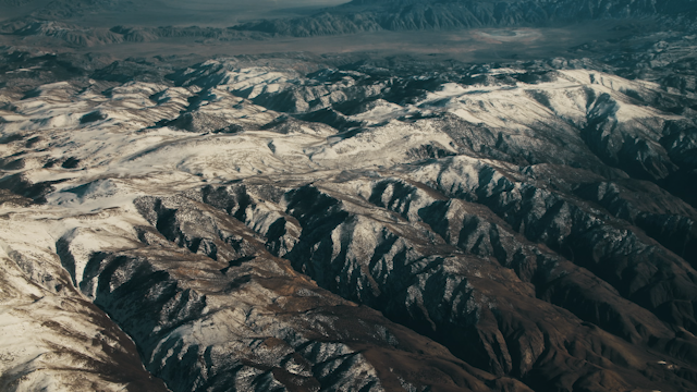 A mountain range with snow passes by below thumbnail