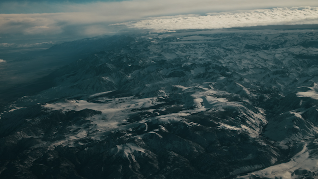 Flying over a large mountain range with clouds and snow thumbnail