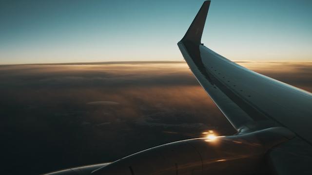 Airplane wing flying through sunset thumbnail