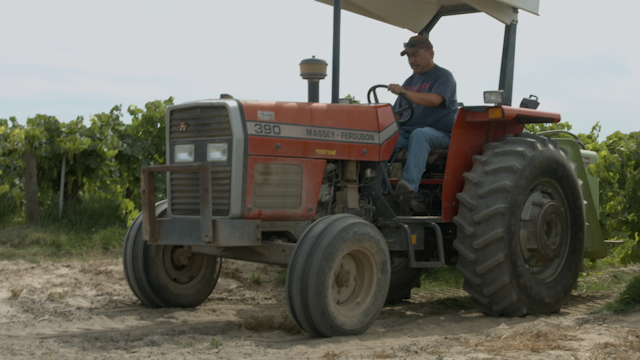 A man tries to fix the engine of his tractor thumbnail