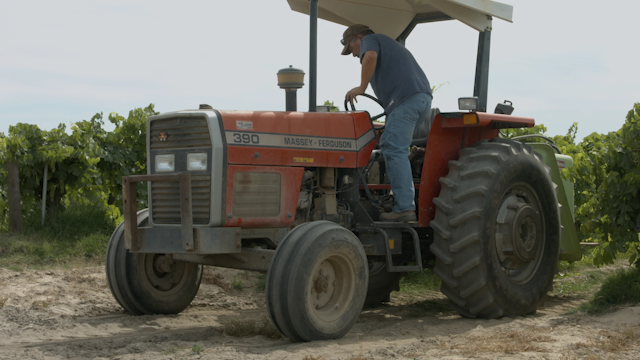 A man uses a wrench to try to fix his tractor thumbnail