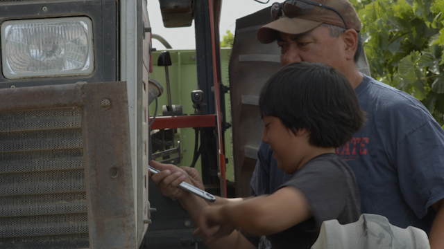 A father shows his son how to fix their tractor thumbnail