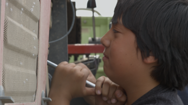 A young boy uses a wrench to try to fix a tractor thumbnail
