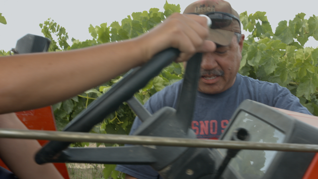 A man shows his son how to operate a tractor thumbnail