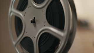 A reel of film is spinning on an old film projector thumbnail