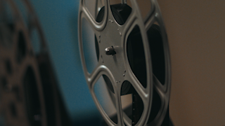 A reel of film slowly spins on an old projector thumbnail