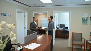 Two businessmen meet and talk in an office thumbnail