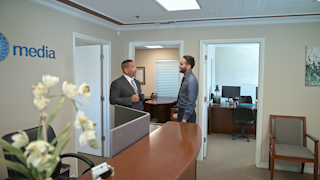 Two businessmen are standing and talking in an office thumbnail