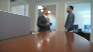 Two businessmen are standing and talking in the background thumbnail