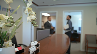 Two businessmen talk in the background in an office thumbnail