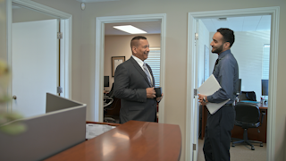 Two businessmen joke with each other in an office thumbnail