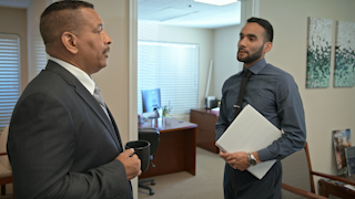 Two businessmen have a discussion in an office thumbnail
