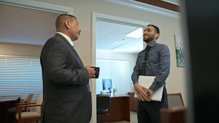 Two businessmen talk with each other in an office thumbnail