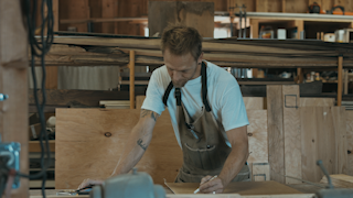 A man is drawing cut lines in his workshop thumbnail