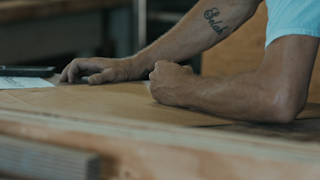 A man is drawing a shape in his workshop thumbnail