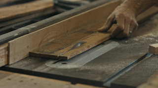 A piece of wood is being sawed in a workshop thumbnail