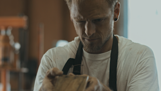 A man is inspecting a piece of wood in his workshop thumbnail