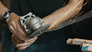 A man is using an angle grinder creating sparks thumbnail