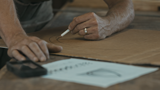 A man is drawing shapes on a piece of cardboard thumbnail