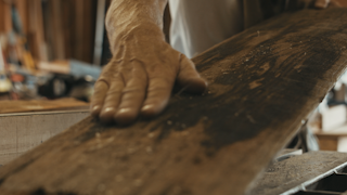 A man inspects and brushes off an old piece of wood in his workshop thumbnail