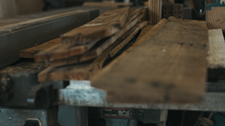 Old pieces of wood are stacked on a workbench thumbnail