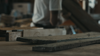 A man carries pieces of wood in the background of his workshop thumbnail