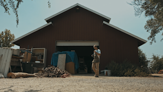 A man walks out of a barn and inspects a pile of sticks thumbnail